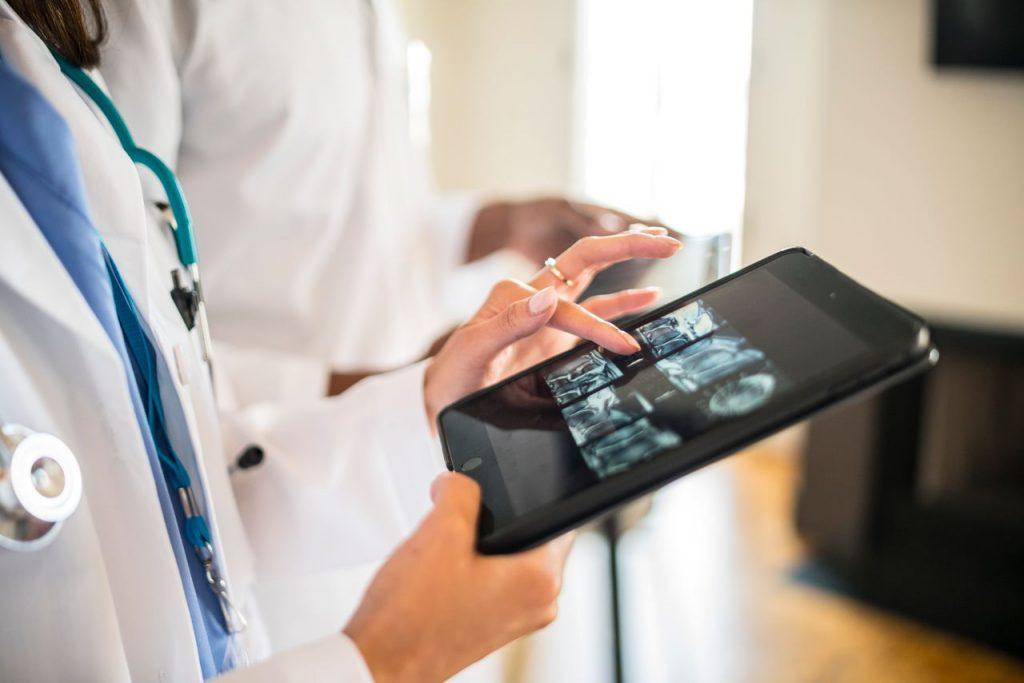 Doctor checking medical data on a tablet, Medical practice management