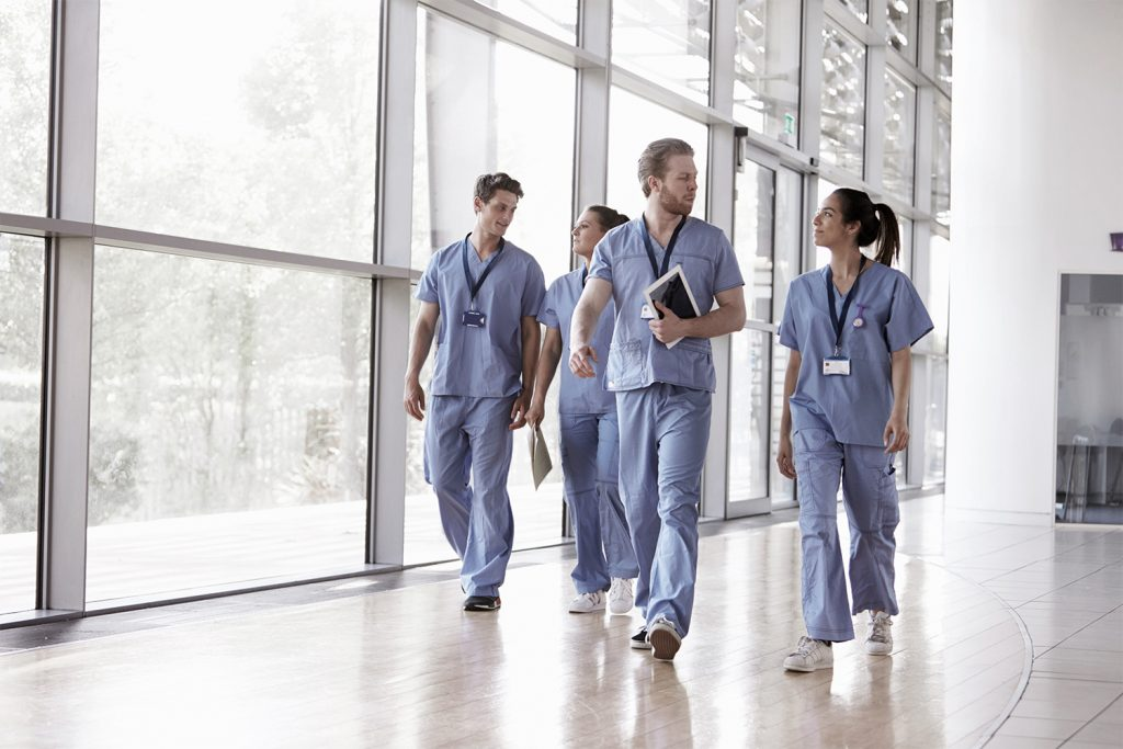 Healthcare professionals walking in the hallway, Medical practice management, Medical Billing and Outsourcing.