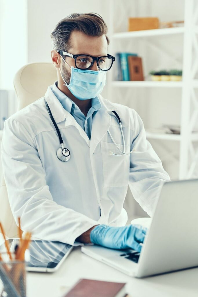 Model Image of a Doctor with a mask on is checking some data on his laptop that relates to his practice.