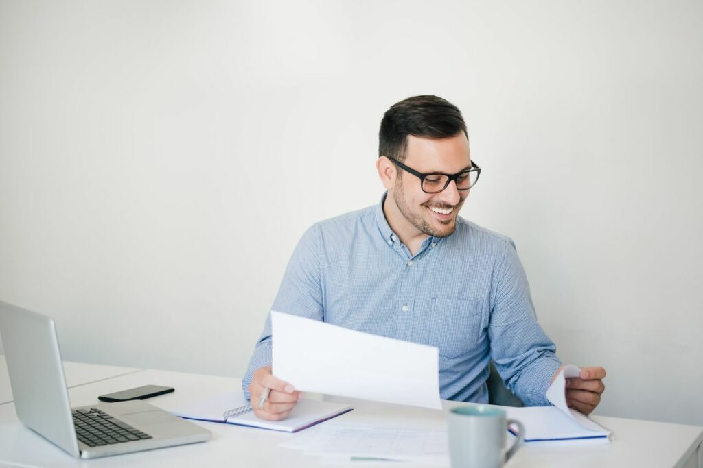 Photo showing a young professional looking happy and satisfied with the information and the data he sees on the paper he is checking.