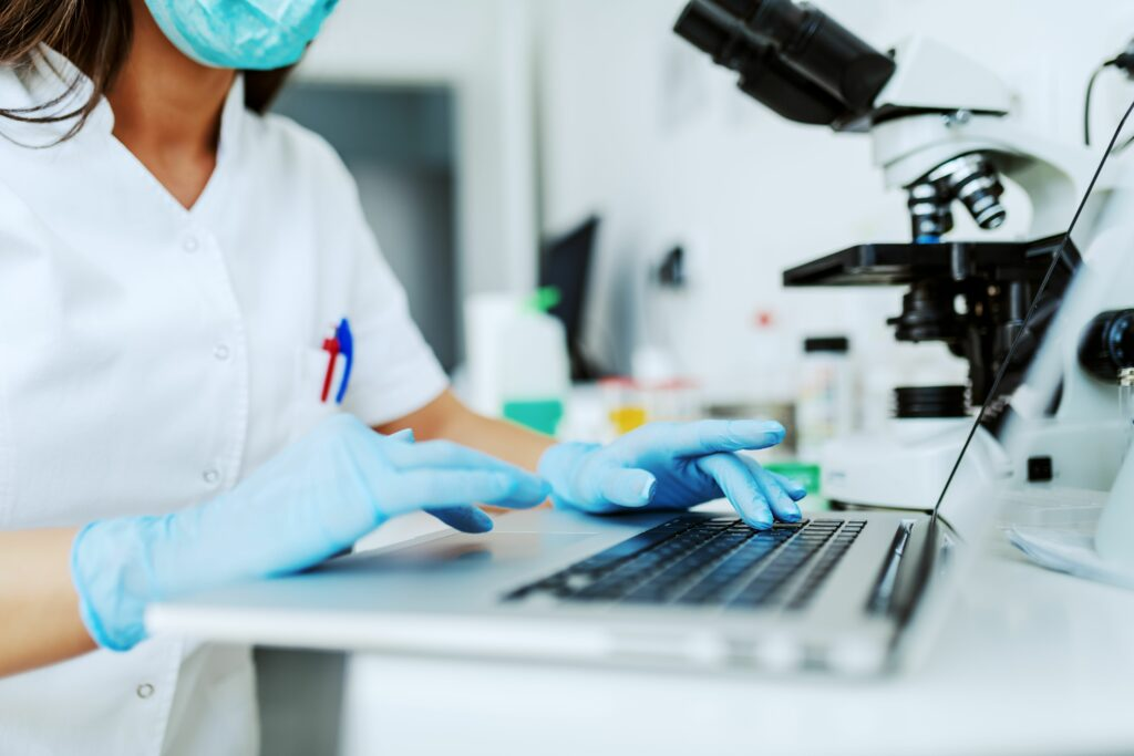 Image showing a masked female medical professional is working in a lab and checking some data on her laptop.